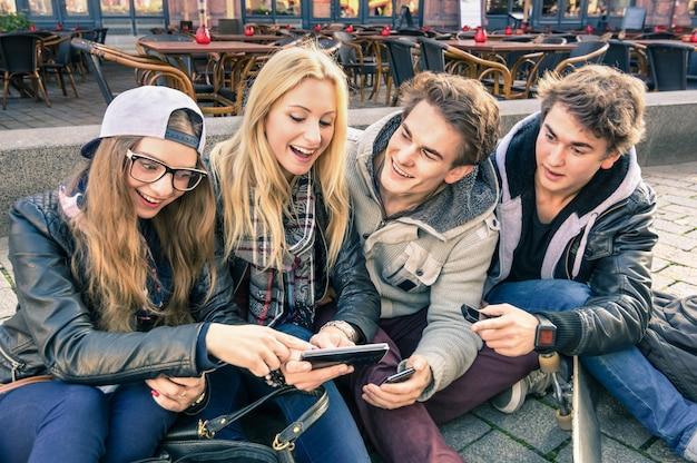 Gruppe junge hippie-freunde, die spaß zusammen mit smartphone haben