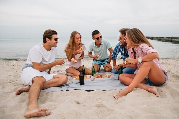 Gruppe junge lächelnde kerle und mädchen, die zusammen auf dem strand, sitzend nahe dem meer stillstehen
