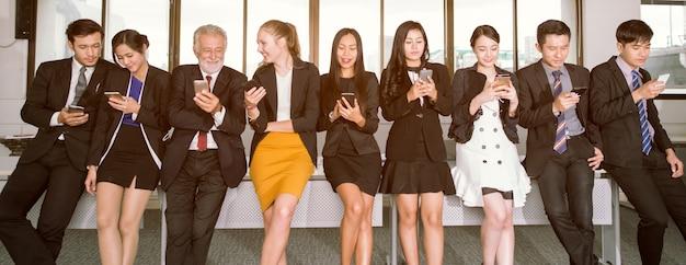 Gruppe junge leute benutzen ihre telefone