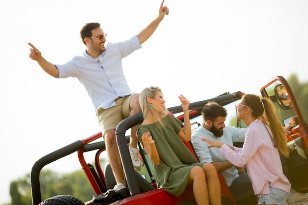 Gruppe junge leute, die den spaß mit dem auto im freien am heißen sommertag haben