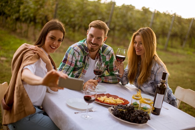 Gruppe junge leute, die durch die tabelle sitzen und rotwein im weinberg trinken