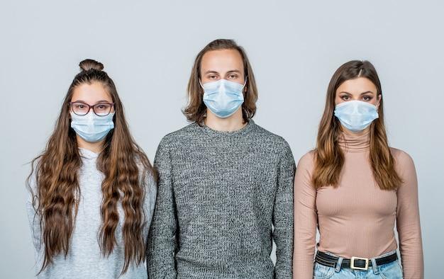 Gruppe junge leute, die eine gesichtsmaske tragen, um den ausbruch des koronavirus zu verhindern