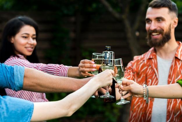 Gruppe junge leute, die mit getränken feiern