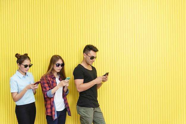 Gruppe junge leute, die smartphone auf wand verwenden. netzwerkverbindungstechnologiekonzept mit