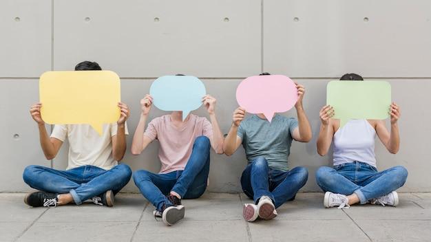 Gruppe junge leute, die spracheblasen halten