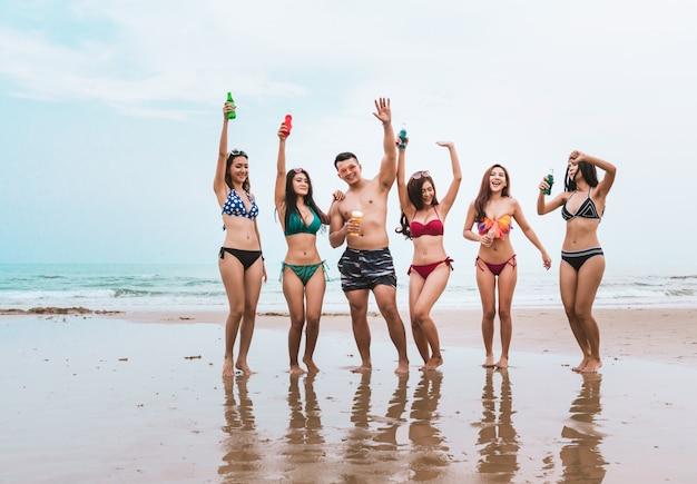 Gruppe junge leute haben spaß, party auf strand in den sommerferien zu trinken und zu tanzen