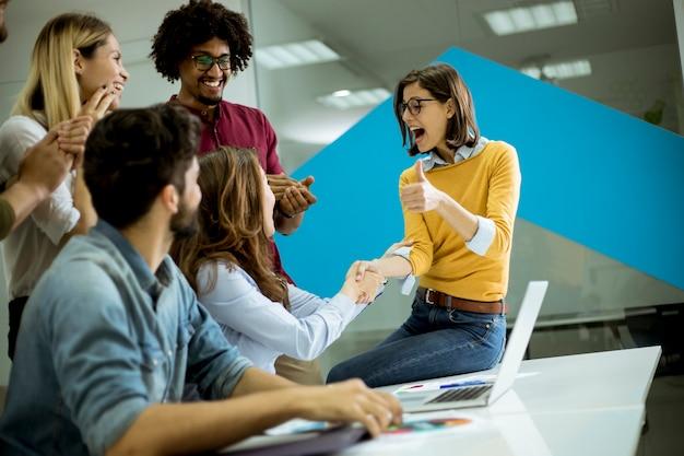 Gruppe junge mitarbeiter, die um einen tisch und ein händeschütteln im büro aufeinander einwirken
