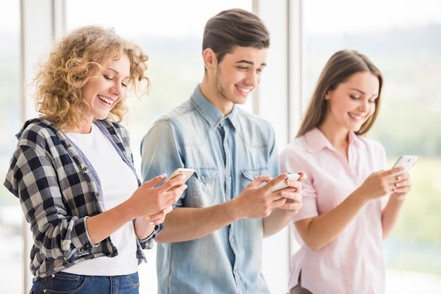 Gruppe junge positive freunde, die ihre telefone verwenden.