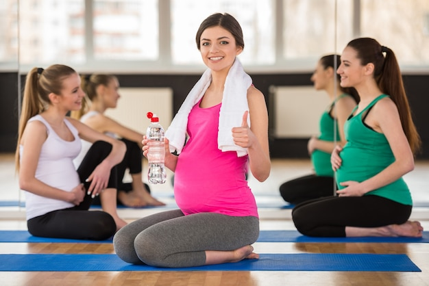 Gruppe junge schwangere frauen an der turnhalle.