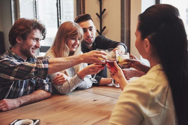 Gruppe junge spaß habende und beim im restaurant bei tisch speisen lachende freunde