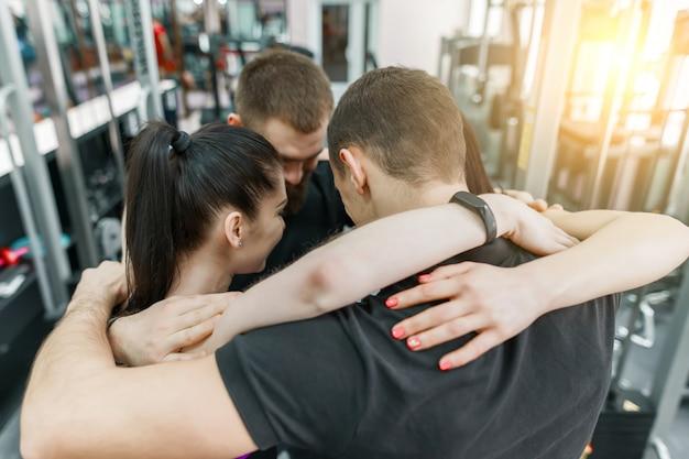 Gruppe junge sportler, die zusammen in den eignungsturnhallenrücken umfassen