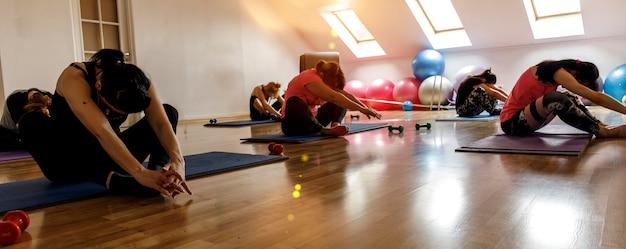 Gruppe junge sportliche attraktive leute, die yogalektion mit lehrer üben.
