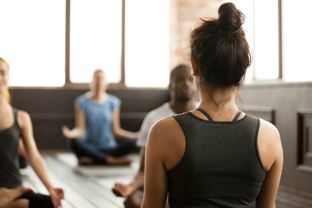 Gruppe junge sportliche leute, die in sukhasana, hintere ansicht sitzen