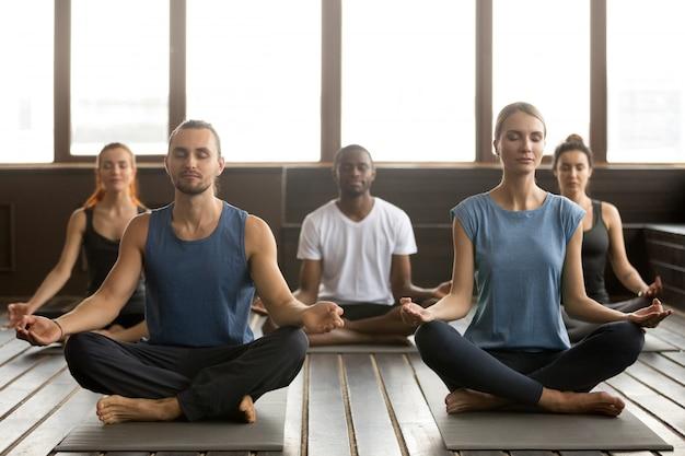 Gruppe junge sportliche leute, die in sukhasana sitzen, trainieren