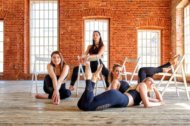 Gruppe junge sportmädchen, die nach einem training in einem geräumigen dachbodenstudio stillstehen