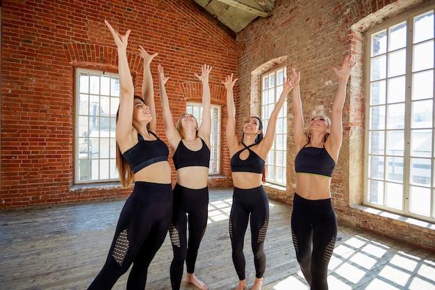 Gruppe junge sportmädchen, die nach einem training in einem geräumigen dachbodenstudio stillstehen.