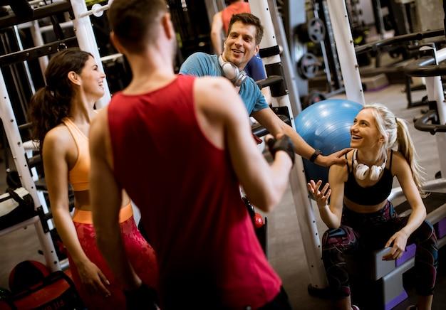 Gruppe junge sprechende und beim auf dem boden der turnhalle nach training zusammen sitzen lachende freunde