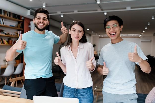 Gruppe junge verschiedene leute, die im büro lächeln
