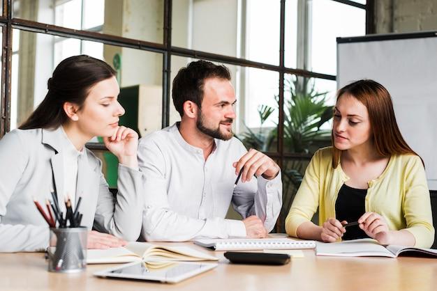 Gruppe junge wirtschaftler, die zusammen an projekt im büro arbeiten