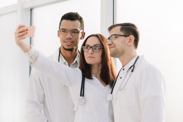 Gruppe junger ärzte, die selfies in der lobby des krankenhauses machen.