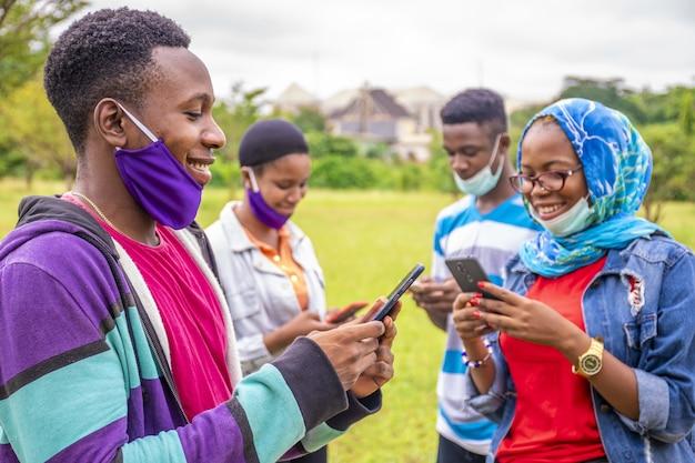 Gruppe junger afrikanischer freunde mit gesichtsmasken, die ihre telefone in einem park benutzen