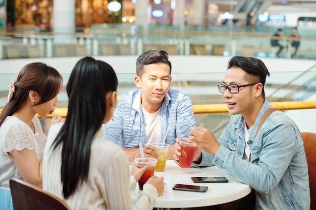Gruppe junger asiatischer leute, die sich im café treffen, um erfrischende getränke zu trinken und aktuelle nachrichten zu besprechen