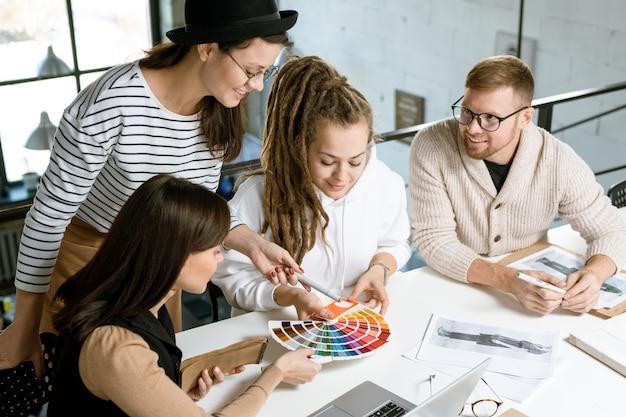 Gruppe junger erfolgreicher designer von kleidung, die beim treffen über trendige farben für ihre neue modekollektion diskutieren