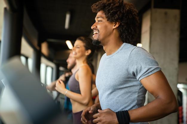 Gruppe junger fitter menschen, die im modernen sportstudio auf laufbändern laufen?