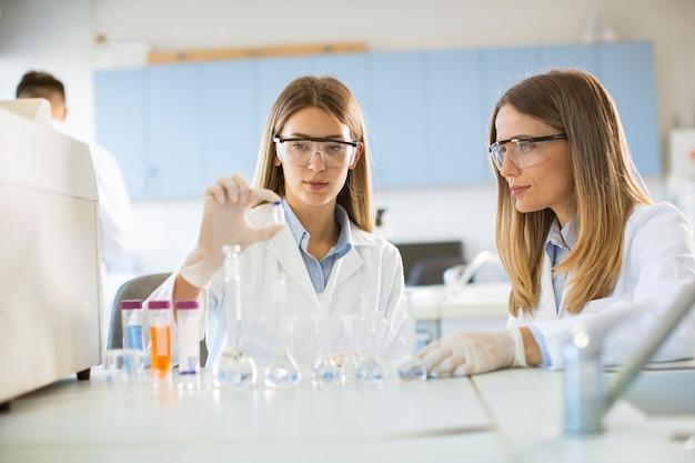 Gruppe junger forscherinnen, die chemische daten im labor analysieren