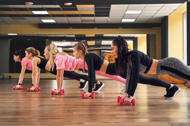 Gruppe junger frauen, die planke auf hanteln zusammen im fitnessstudio tun