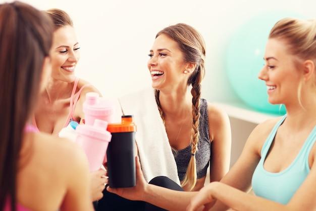 Gruppe junger frauen, die sich nach dem training im fitnessstudio ausruhen