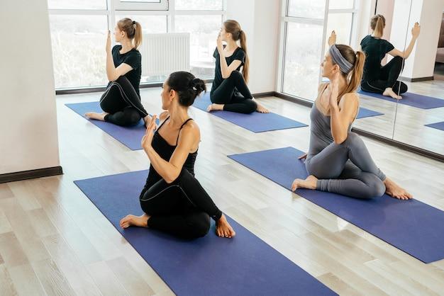Gruppe junger frauen, die yoga-übungen im studio machen und stretching-posen im unterricht drinnen machen