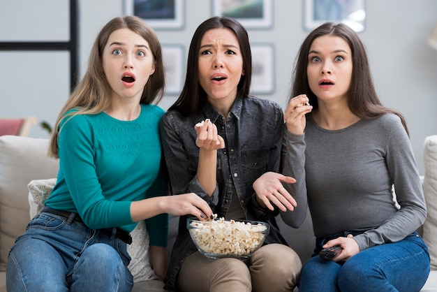 Gruppe junger frauen, die zusammen einen gruselfilm sehen