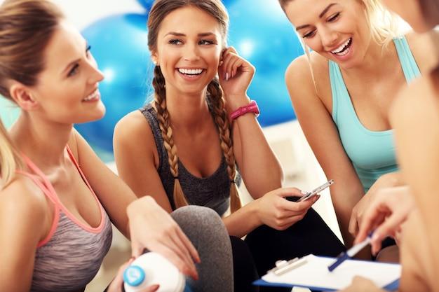 Gruppe junger frauen diskutiert trainingsplan im fitnessstudio