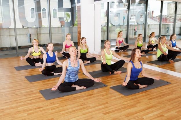 Gruppe junger frauen im yoga-kurs