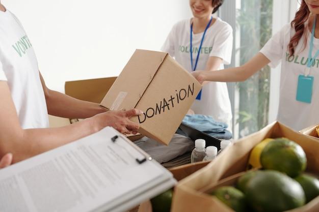Gruppe junger freiwilliger, die im spendenzentrum arbeiten, sie packen lebensmittel und kleidung für bedürftige
