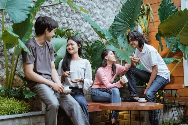 Gruppe junger freunde, die getränke im freien eines hauses genießen