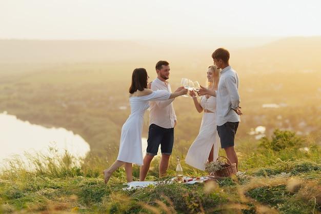 Gruppe junger freunde, die spaß daran haben, während eines picknicks mit weingläsern anzustoßen