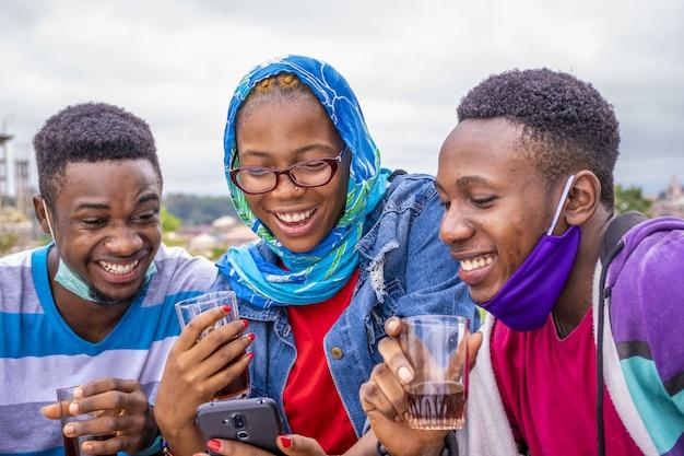Gruppe junger freunde, die wein trinken und ihre telefone in einem park benutzen