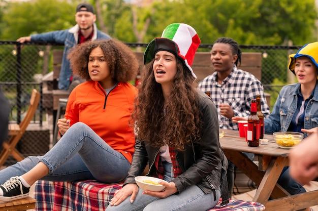 Gruppe junger freundlicher fußballfans, die nervös sind, während sie sendung im freien sehen