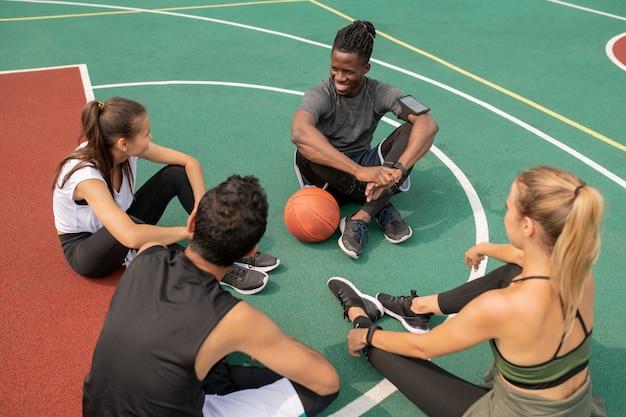 Gruppe junger freundlicher interkultureller leute, die auf spielplatz sitzen, während sie sich für ein anderes basketballspiel vorbereiten