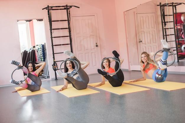 Gruppe junger fröhlicher frauen, die pilates-übungen mit fitnessringen machen