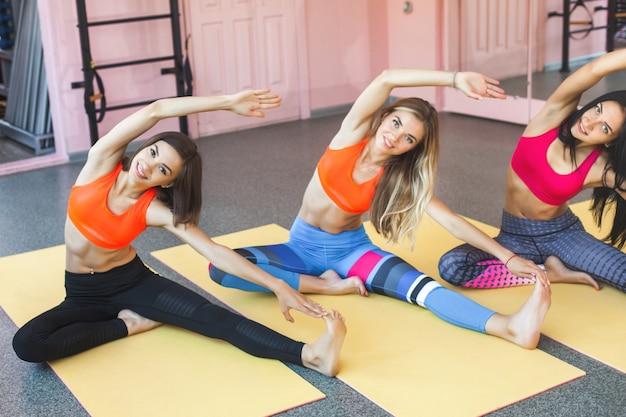 Gruppe junger fröhlicher frauen, die yoga-klasse haben