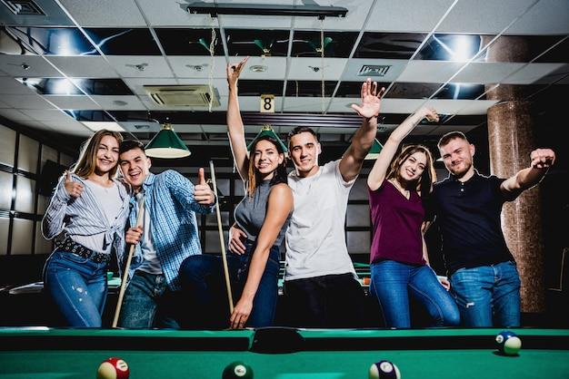 Gruppe junger fröhlicher freunde, die billard spielen.