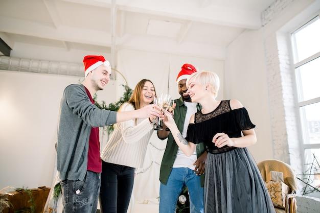 Gruppe junger gemischtrassiger freunde in weihnachtsmützen an silvesterparty, die einen toast machen, der gläser champagner anhebt
