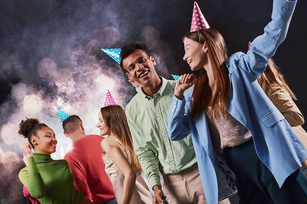 Gruppe junger, glücklicher, gemischtrassiger menschen, die geburtstagshüte tragen, lachen und spaß haben