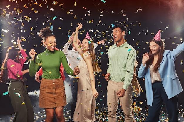 Gruppe junger, glücklicher, gemischtrassiger menschen, die geburtstagshüte tragen, tanzen und spaß mit konfetti haben