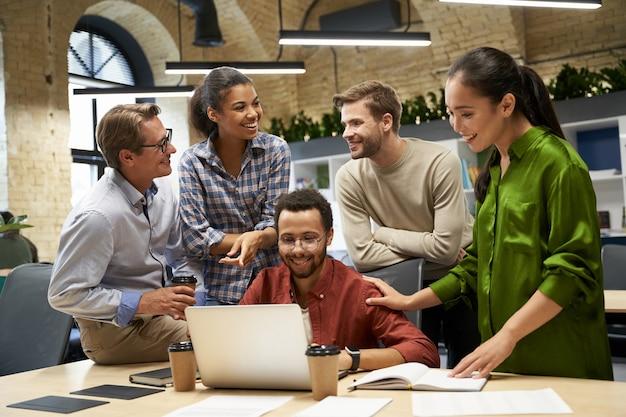 Gruppe junger glücklicher geschäftsleute, die auf laptop-bildschirm schauen, kommunizieren und über arbeit diskutieren