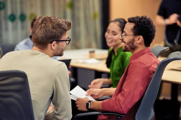 Gruppe junger, glücklicher, multiethnischer mitarbeiter, die während der zusammenarbeit ideen austauschen und austauschen