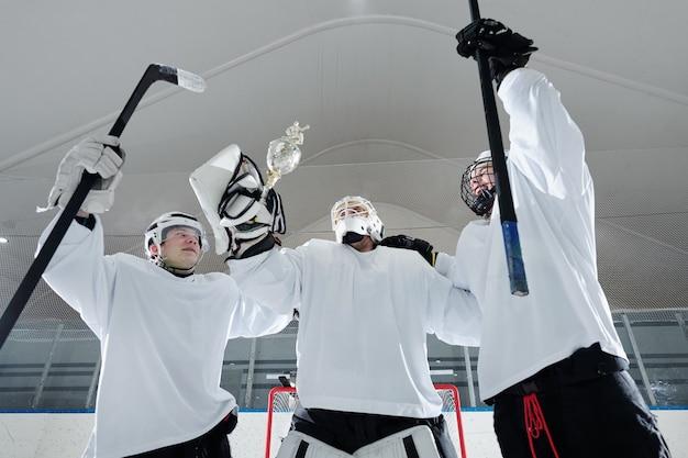 Gruppe junger hockeyspieler in sportuniform, handschuhen und schutzhelmen, die stöcke und siegerpokal halten, während sie vor der kamera stehen